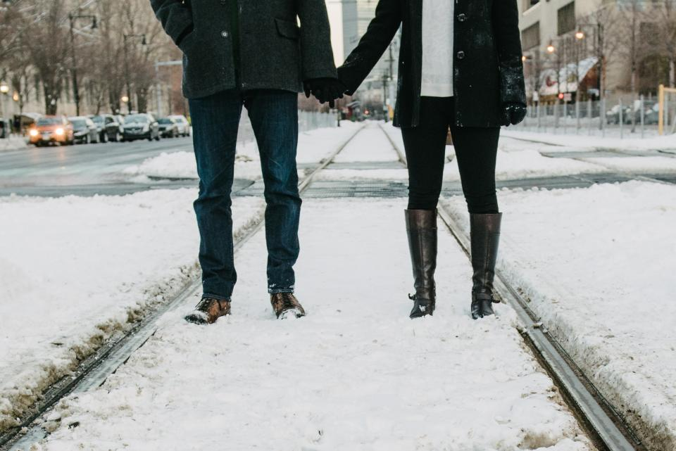 couple love romance holding hands girl woman guy man people snow boots winter cold city urban streets roads