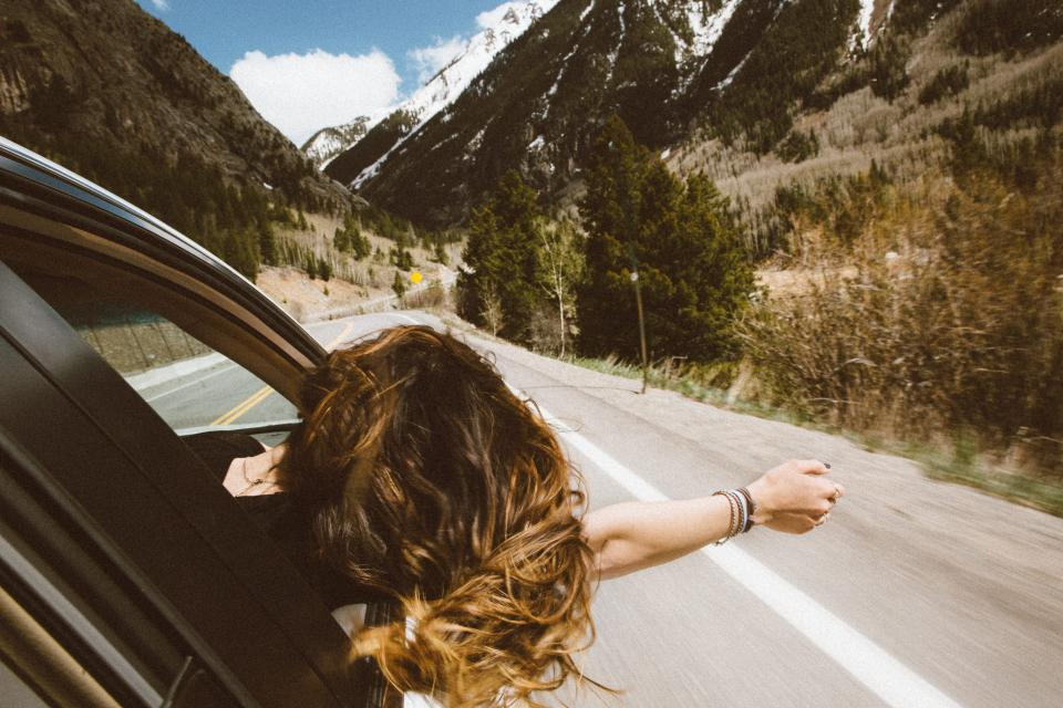 woman girl lady people ride arm out curls car road street path trip countryside trees plants bushes mountains perspective
