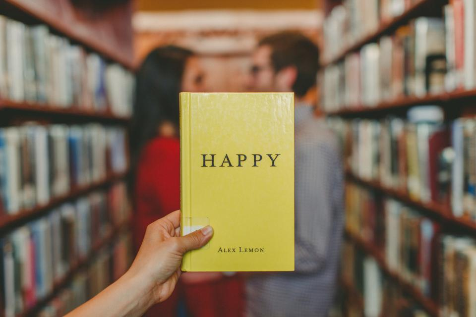 man woman couple people hands hold books alex lemon yellow library shelves still bokeh happy