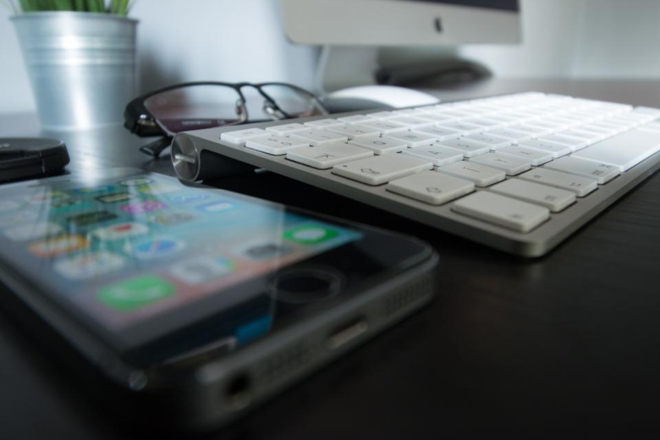 office work workspace business desk table gadgets iphone smartphone mobile reflection mac computer keyboard monitor mouse reading glasses pot plant still bokeh