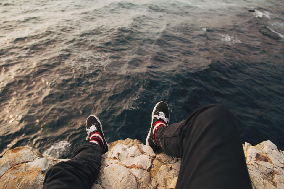 sea ocean water waves nature rocks coast sneakers people man sitting