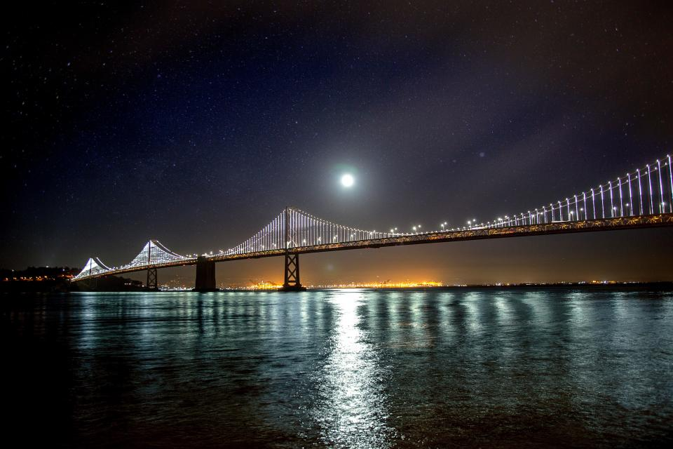 architecture bridge structure blue sky dark night stars moon view horizon river sea water reflection lights city
