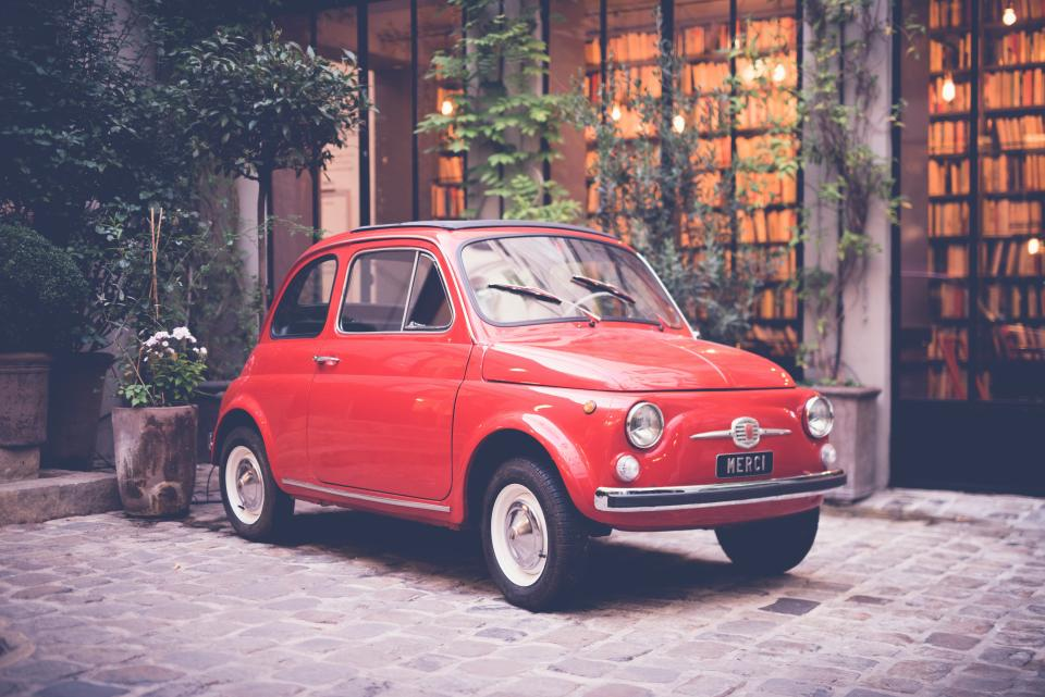 red car auto vehicle travel outside outdoor park house green plant nature