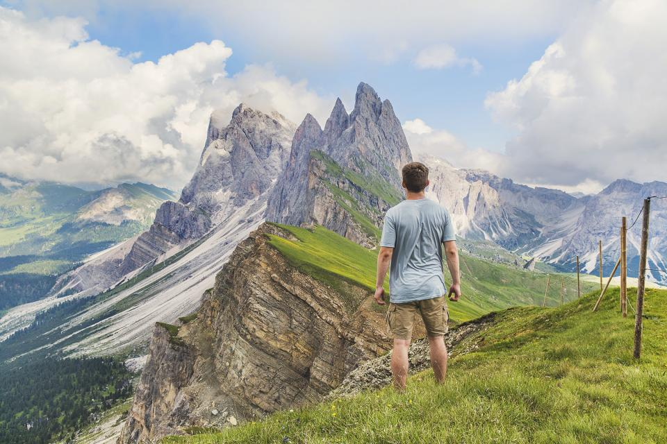 guy man travel wanderlust grass field mountains landscape scenery sky clouds adventure people