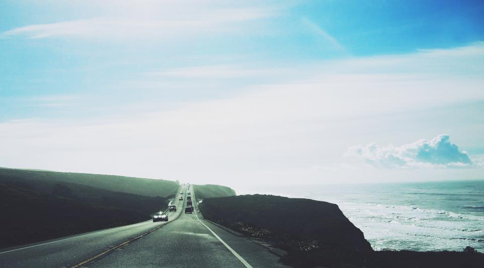 road highway cars ocean sea waves blue sky pavement