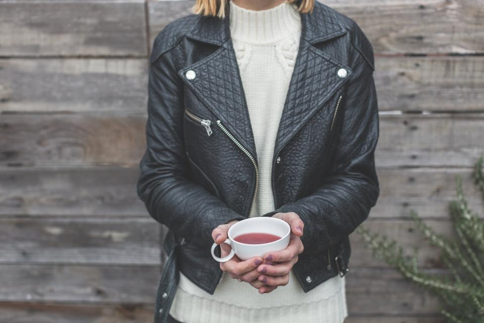 people female girl woman drink cup tea healthy lifestyle black leather jacket wooden wall outdoor