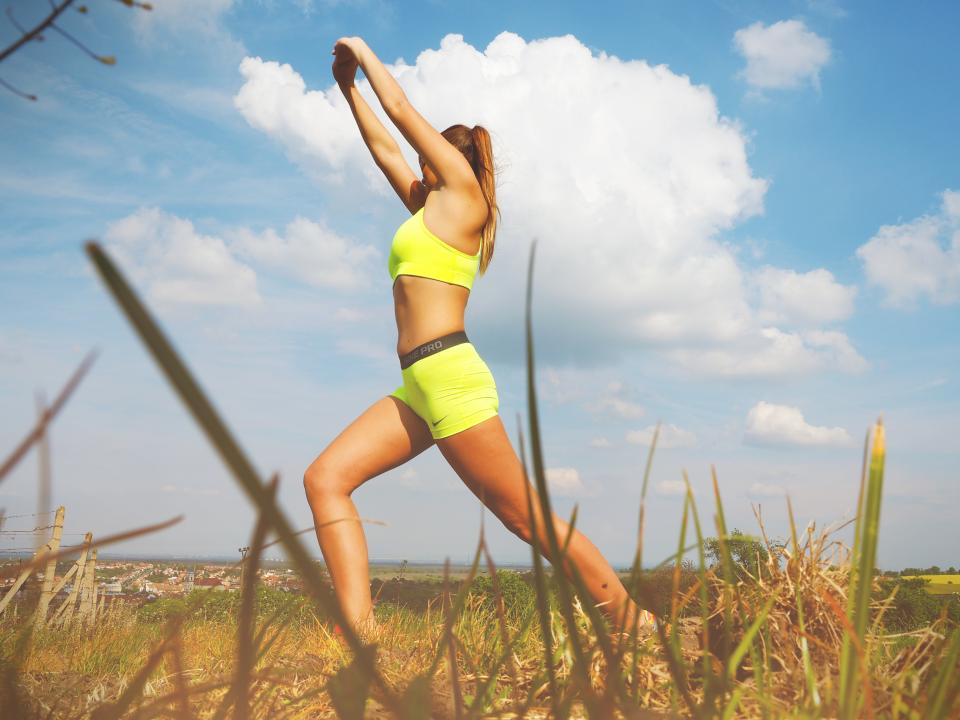 people woman fitness healthy exercise clouds sky grass fit athlete