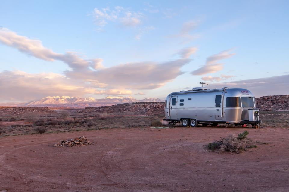 nature landscape desert dirt soil camp rocks sky clouds horizon RV trailer house transportation