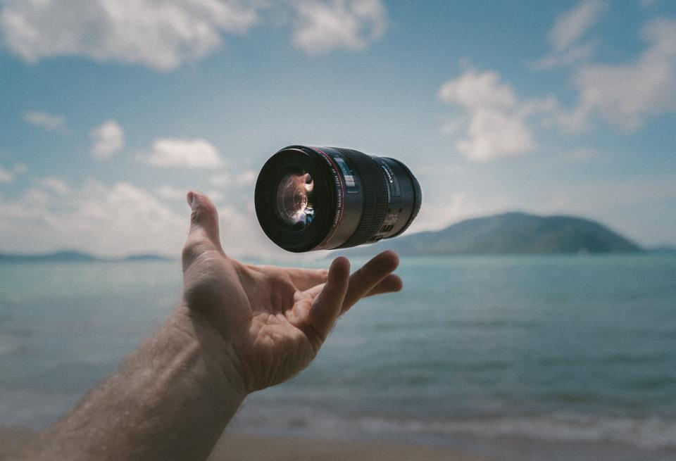 camera lens accessory sea water hands palm nature