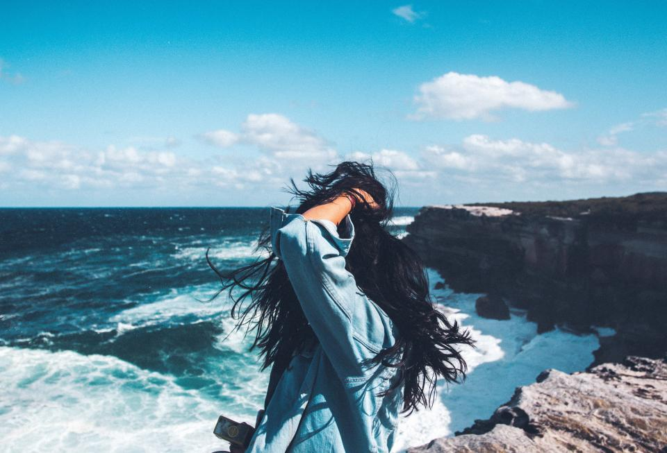 sea ocean water waves nature blue sky clouds horizon coast hill rock people girl alone sunny day