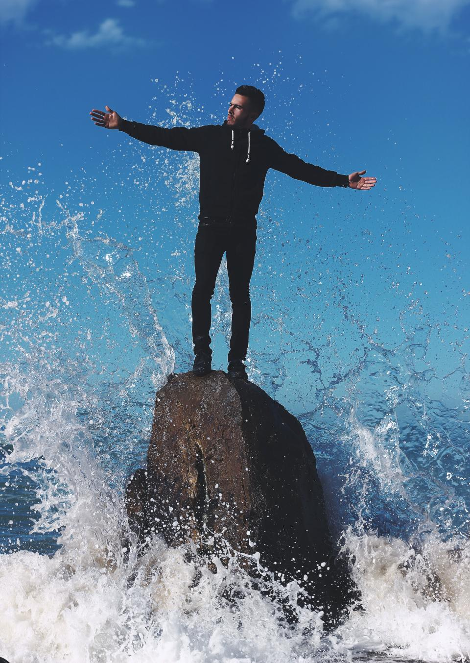 guy man wave water splash rock formation beach sea hoodie sky black people
