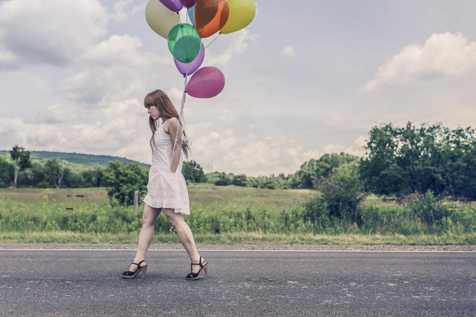 girl woman balloons high heels dress legs redhead hair walking country road grass fields trees green sky clouds