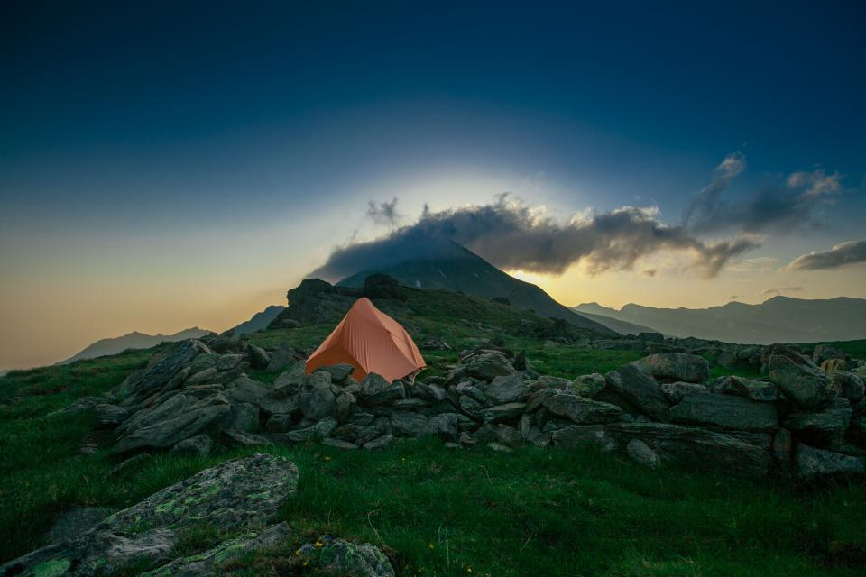 mountain highland cloud sky summit ridge landscape nature valley green grass rocks tent outdoor trravel