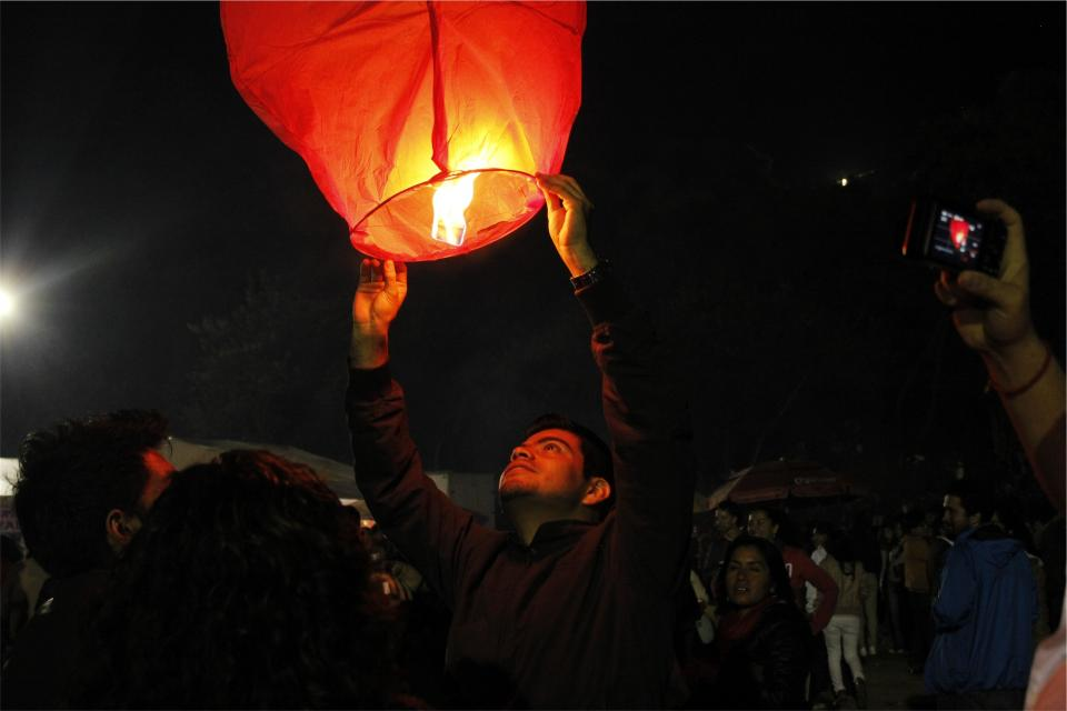 fire lantern dark night people crowd spectators photographers man guy