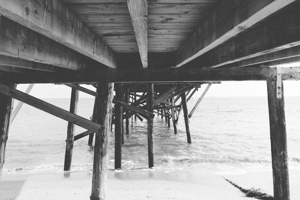wood dock pier beach sand water ocean black and white