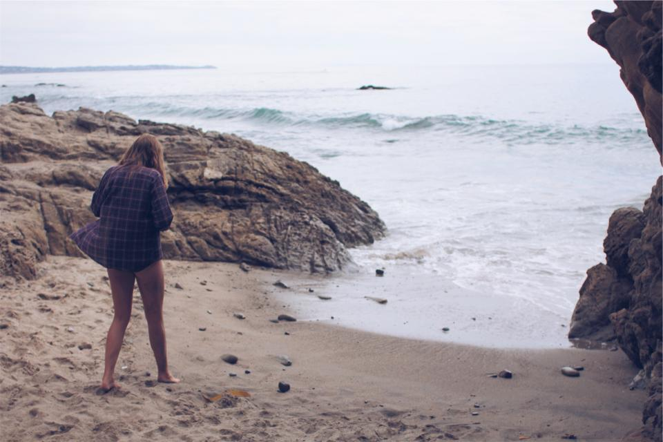 beach sand water waves shore young girl people plaid shirt legs