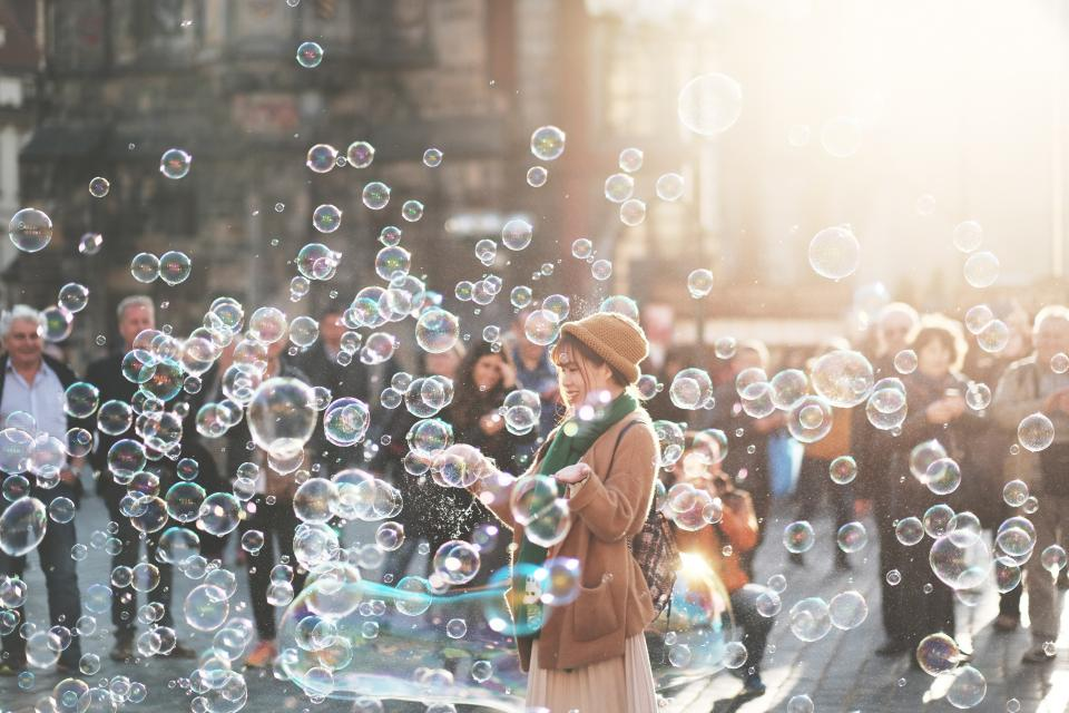 people crowd girl men water bubbles street sunlight sunny