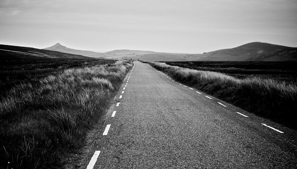 road rural country empty fields grass plants mountains hills valleys landscape black and white