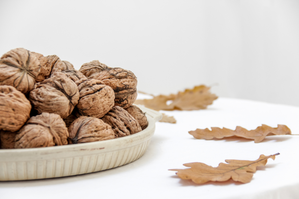 walnuts plate table leaves oak close up healthy snack diet nuts harvest organic natural food ingredients raw minimal