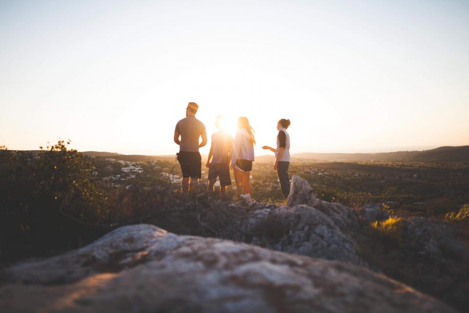 people friends group sunset dusk field rocks grass nature outdoors adventure wanderlust