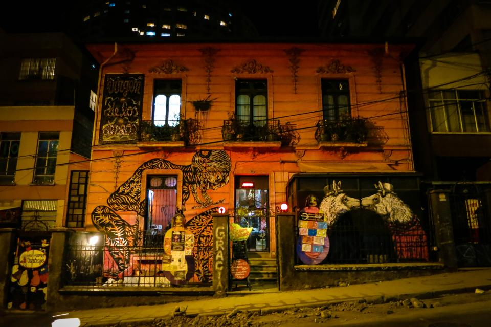 Building in La Paz Bolivia graffiti mural art spray paint building windows railings sidewalk dark night entrance