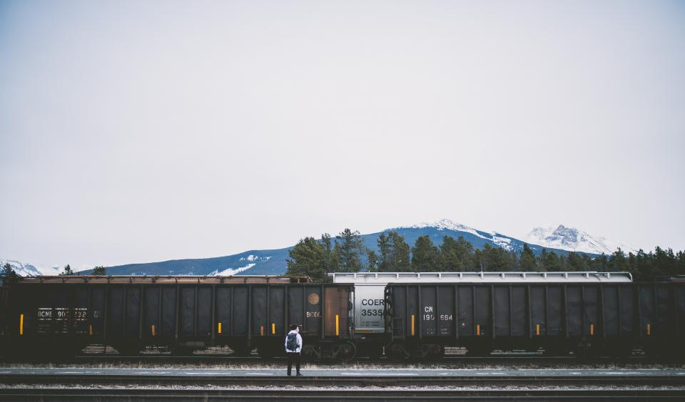 railway track train transportation travel outdoor people guy man waiting outside mountain view landscape sky trees
