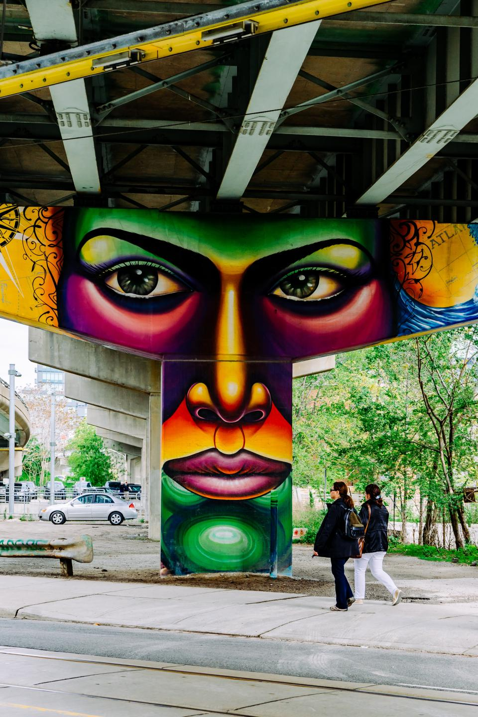 public bridge infrastructure wall street art mural painting graffiti people walking outdoor trees plants