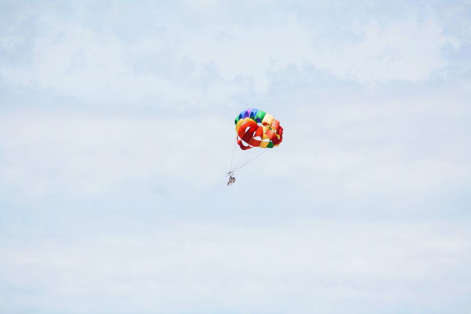 colorful parachute blue sky clouds people fly parasailing adventure