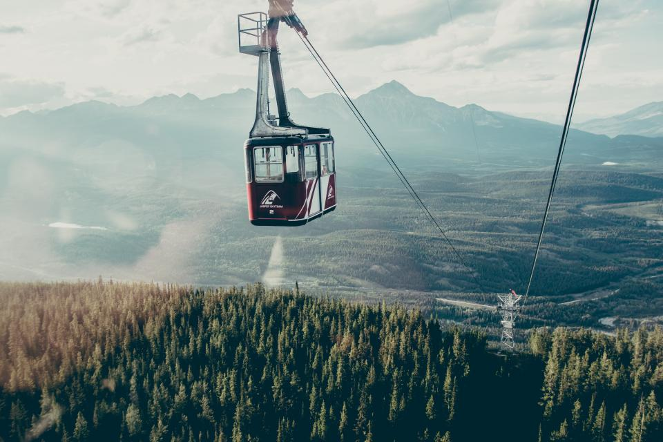 gondola lift cables mountains landscape nature trees fields forest sky sunshine sunlight adventure outdoors clouds
