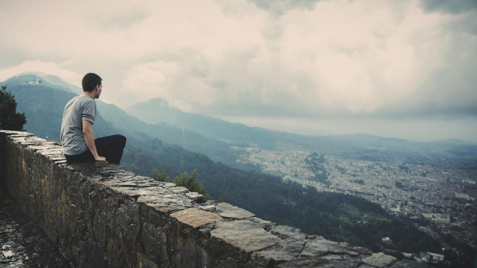 guy looking sitting ledge city town mountains valleys hills clouds view people