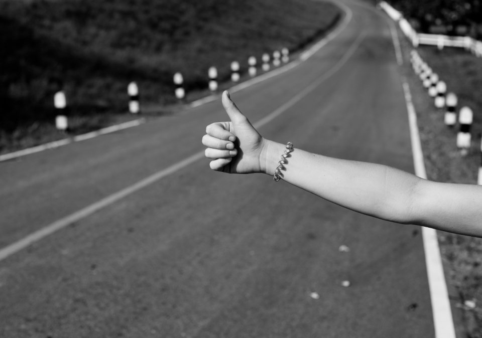 arm gesture hand help highway hitchhike ride road sign symbol thumb transportation travel waiting