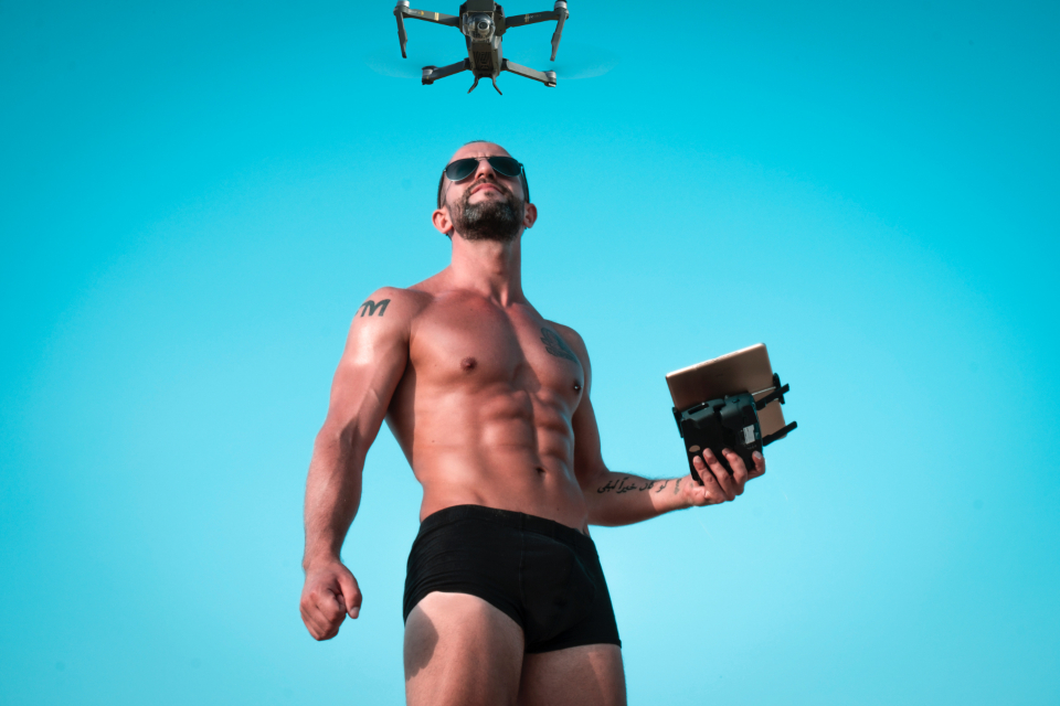 man shorts drone muscles strong powerful fly technology remote blades sunglasses male tan tattoo blue sky