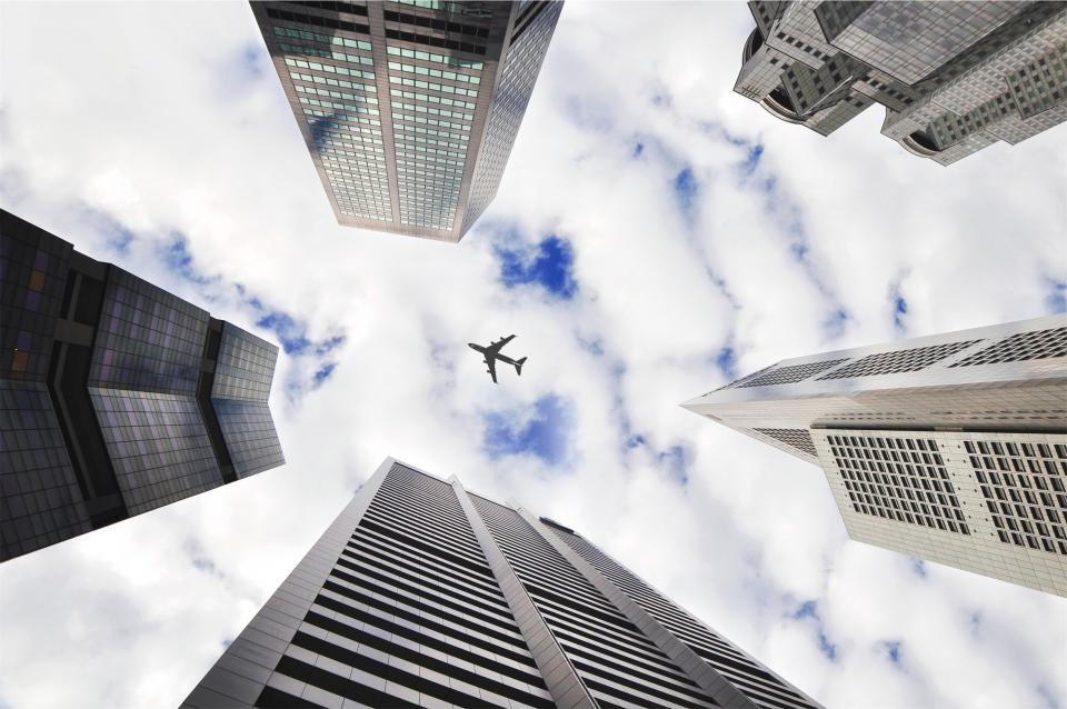 airplane sky buildings towers architecture city clouds transportation travel trip