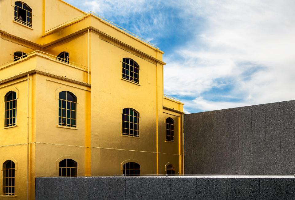 architecture yellow building structure blue sky clouds wall