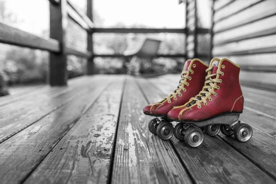 red roller skates laces wheels wood deck porch