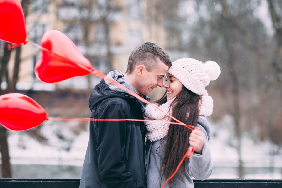 people man woman couple happy love date cold winter weather snow balloons heart red smile