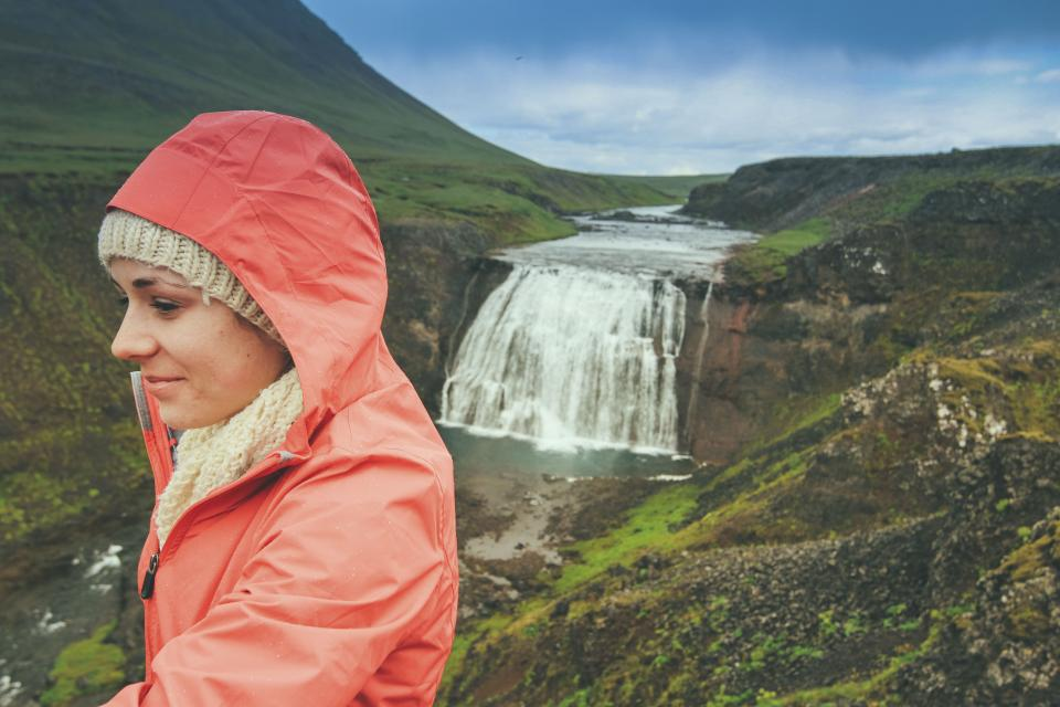 waterfall stream water nature green grass landscape rocks moss view people girl woman orange hood travel highland blue sky