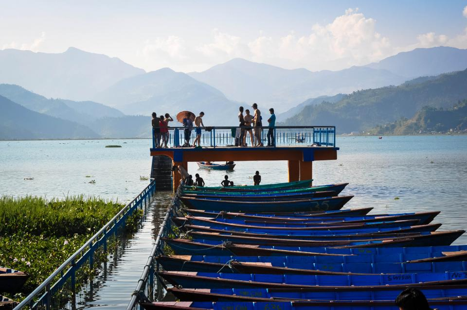 boats docks pier water swimming people kids lake water mountains hills Fewa Lake Pokhara Nepal