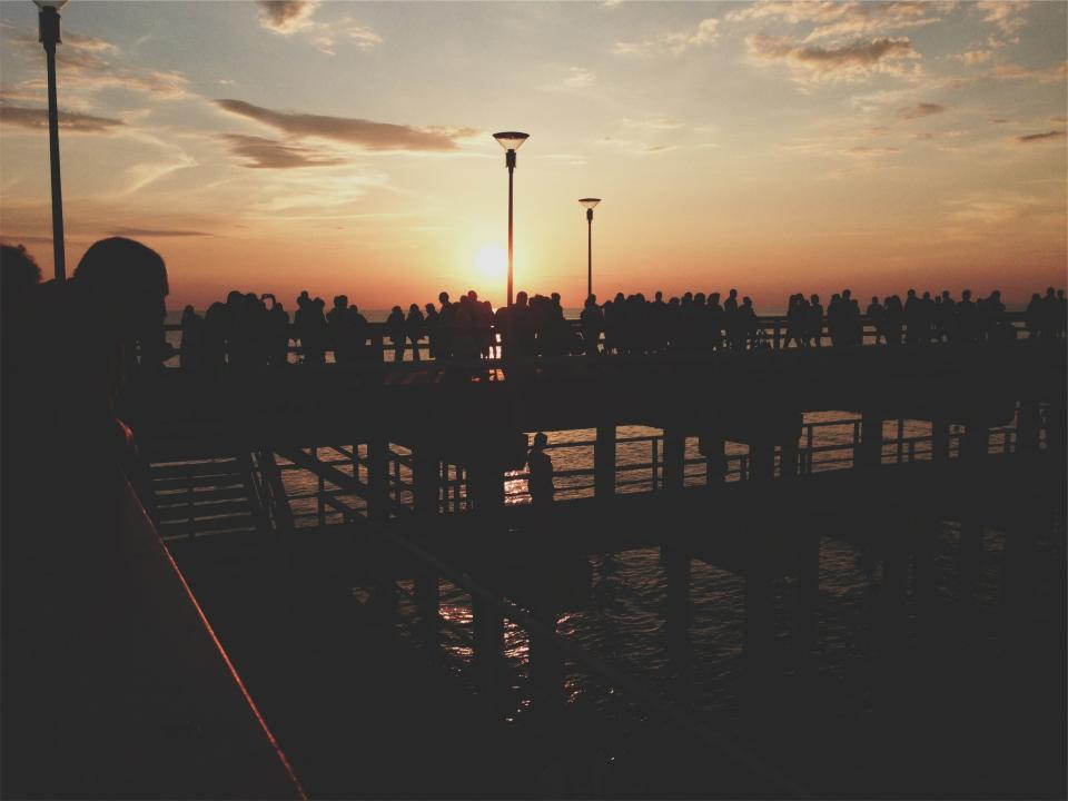 sunset pier people crowd dusk silhouette shadows sky lamp posts