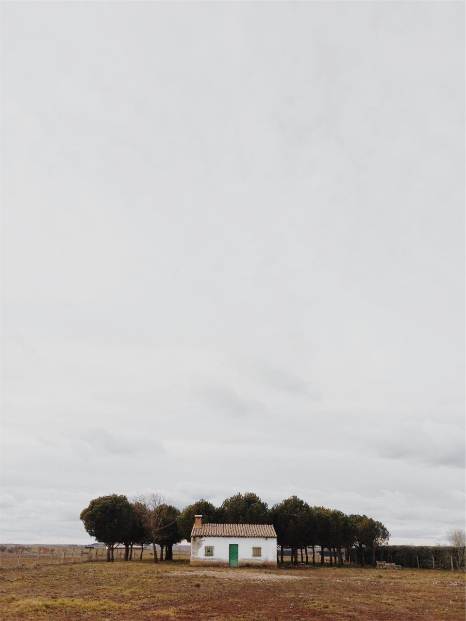 rural house dirt trees grass fence country grey sky cloudy