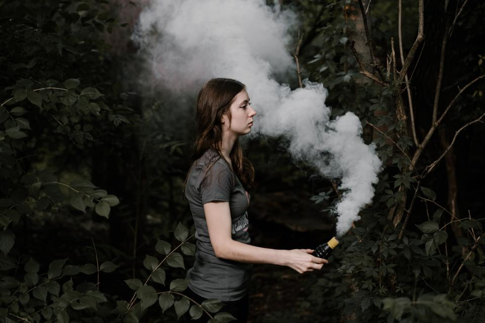 people women lady hand bottle smoke gas trees forest nature leaves branches white green