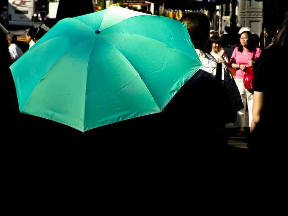 green umbrella crowd people pedestrians