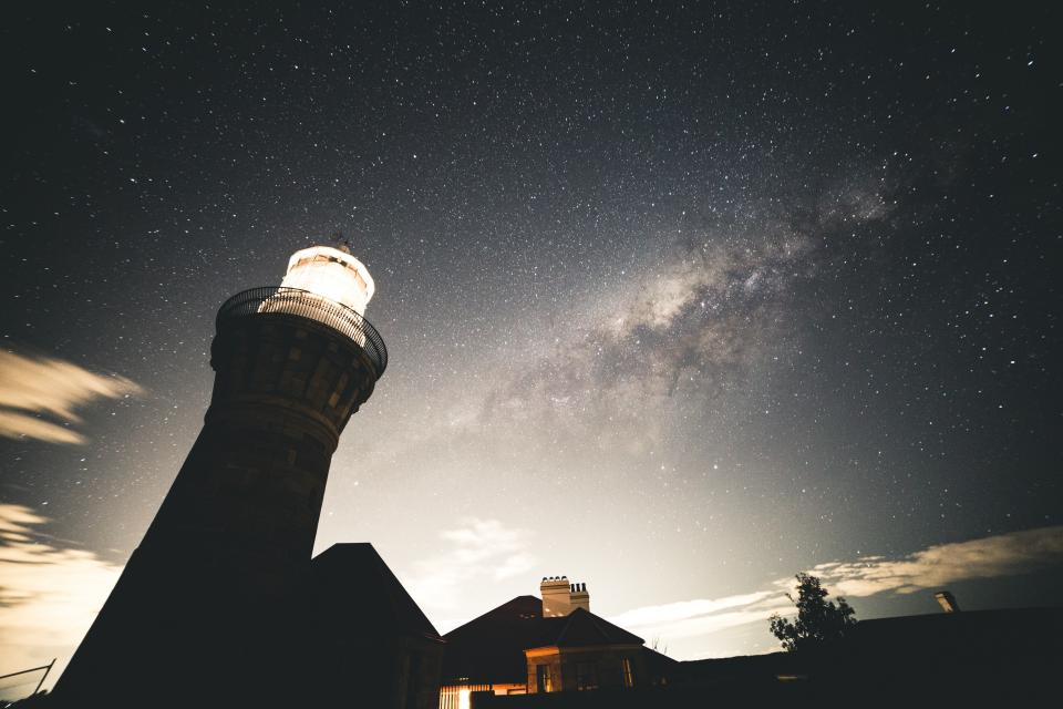 lighthouse dark night sky stars galaxy clouds house lights