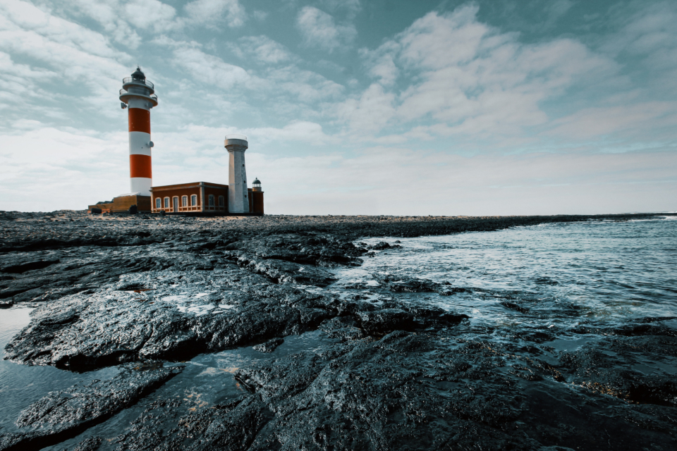 lighthouse sea day ocean water sky rocks building architecture