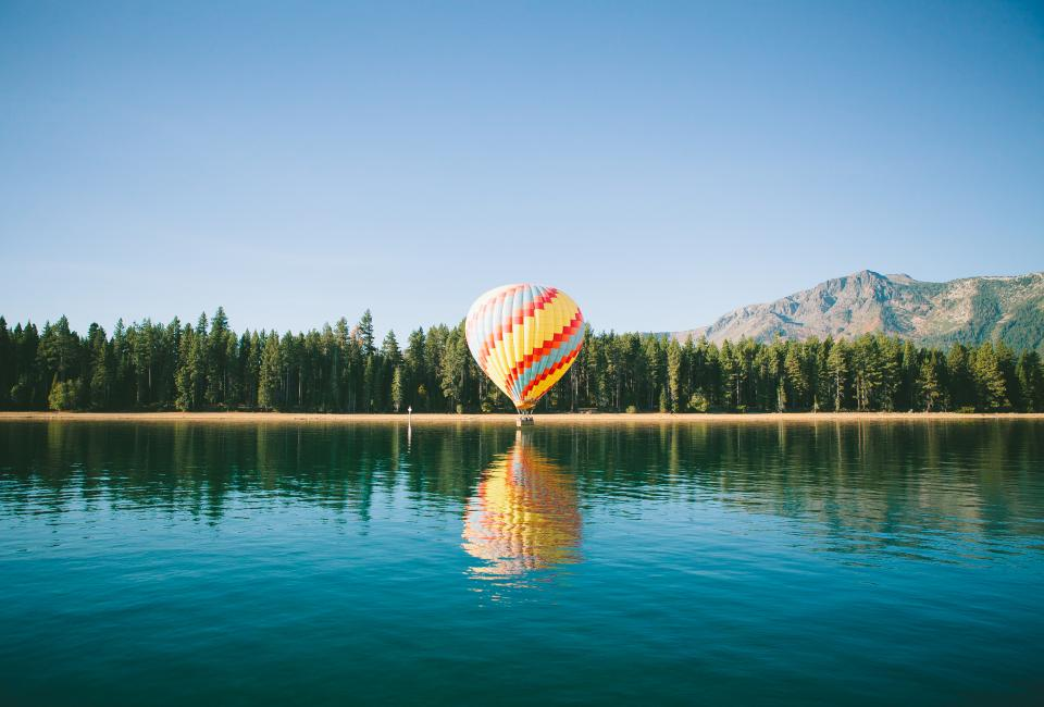 hot air balloon blue sky lake water reflection trees plant horizon mountain landscape view
