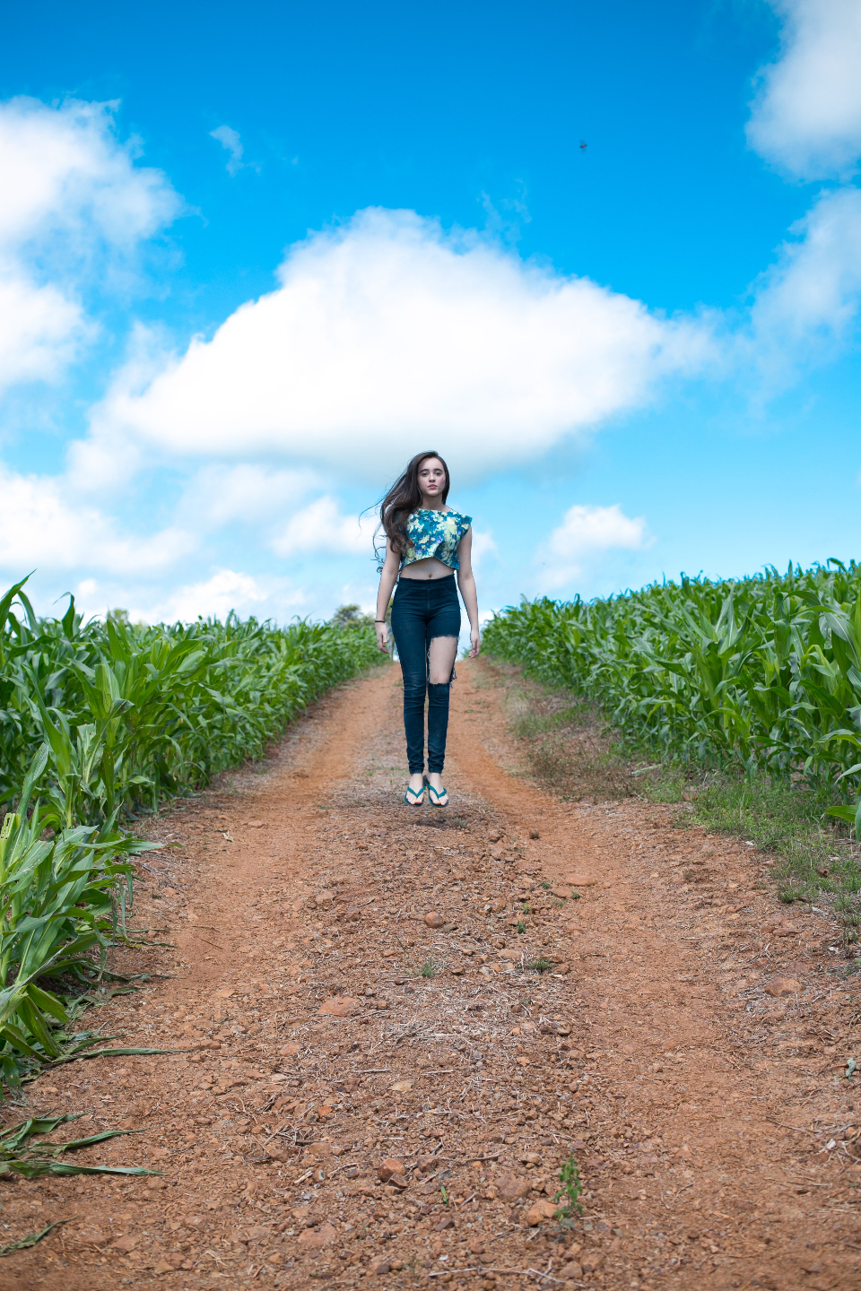 girl jumping field farm crops path track woman female summer blue sky clouds stones