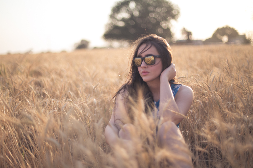 woman sitting field sunglasses reflection people yound think farm tree
