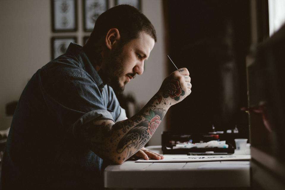 people man tattoo drawing design artist art pen paper table concentrate