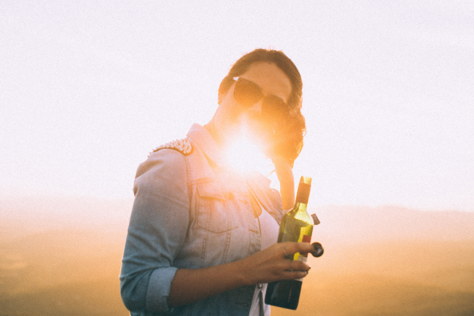 woman holding bottle wine wine red wine drink alcohol sunglasses summer happy smile sunset sunlight female girl