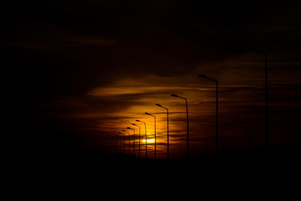 nature sky dusk dawn sunset sunrise sun sinister clouds row line lamps light posts silhouette shadows